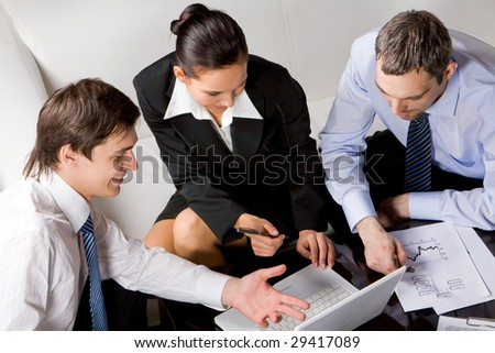 Photo of successful businessman explaining his point of view to colleagues at meeting - stock photo