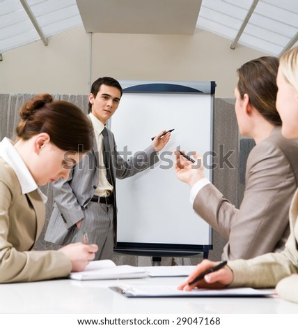 Photo of successful businessman sharing ideas by whiteboard and communicating with partners at presentation