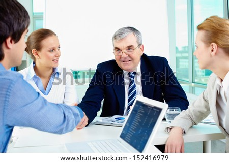 Photo of successful businessmen handshaking after striking deal with female partners near by - stock photo