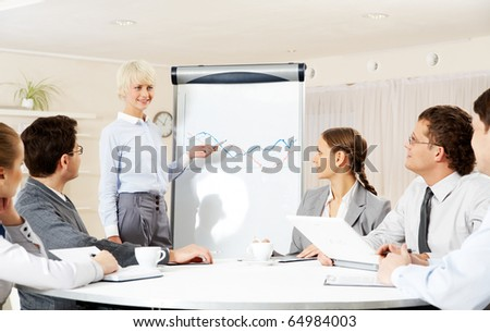 Photo of successful businesswoman reading lecture to colleagues at presentation of new project - stock photo
