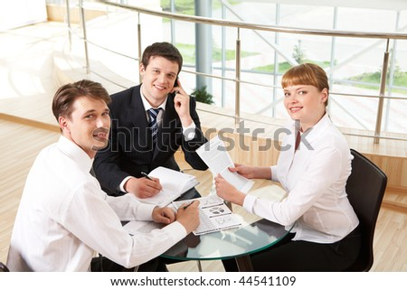 Photo of successful co-workers gathered around table and looking at camera during meeting - stock photo