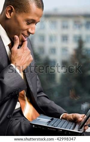 Photo of successful employee looking at laptop display during work - stock photo