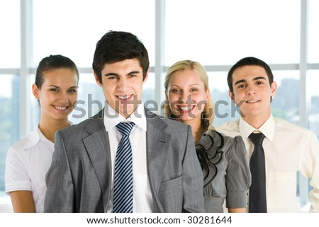 Photo of successful employer looking at camera with his colleagues at background