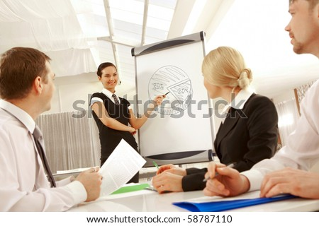 Photo of successful female standing by whiteboard and pointing at diagram on it at seminar - stock photo
