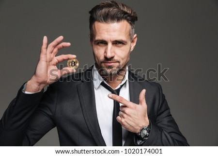 Photo of successful mature man with brown hair in suit and tie advertising and pointing finger on golden bitcoin isolated over dark gray background
