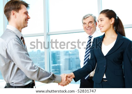 Photo of successful partners handshaking after signing agreement