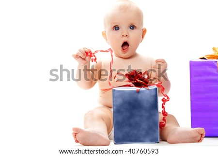 Photo of surprised baby sitting with big giftbox by her side over white background - stock photo