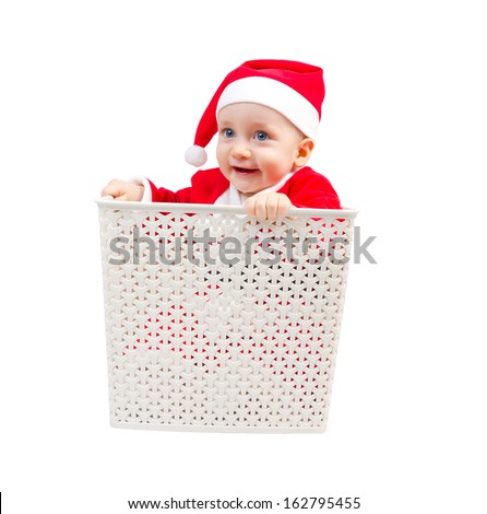 Photo of surprised boy in Santa Clause suit hiding in a box isolated on white background