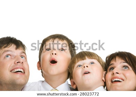 Photo of surprised family members looking upwards with excitement - stock photo