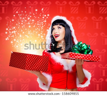 Photo of surprised snow maiden with a christmas gift with magic shining from box - studio red background - stock photo
