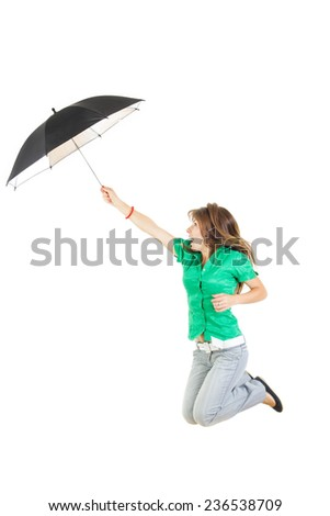Photo of surprised young woman or girl in green shirt and gray jeans pants with umbrella jumping in air up studio isolated on white . Carefree and freedom concept - stock photo