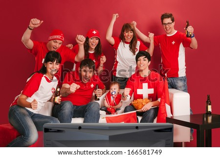 Photo of Swiss sports fans watching television and cheering for their team. - stock photo