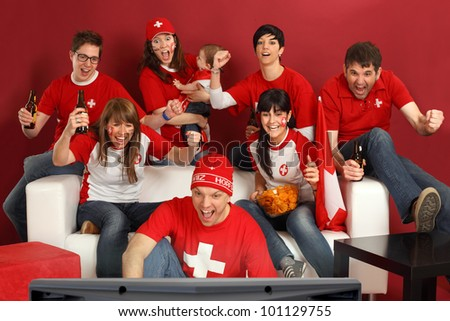 Photo of Swiss sports fans watching television and cheering for their team. Hopp Schwiiz! - stock photo
