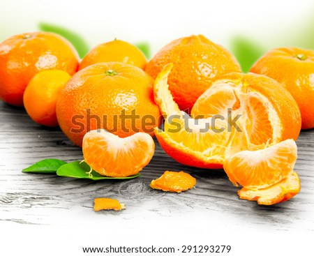 Photo of tangerines with slices and leaves on wooden board with white space