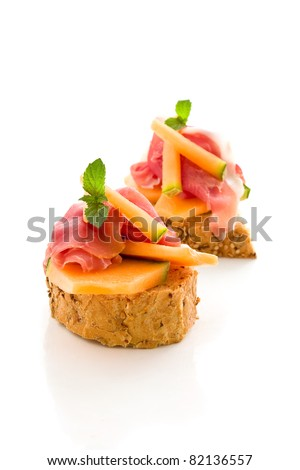 photo of tasty bread slices with bacon and melon on isolated background - stock photo