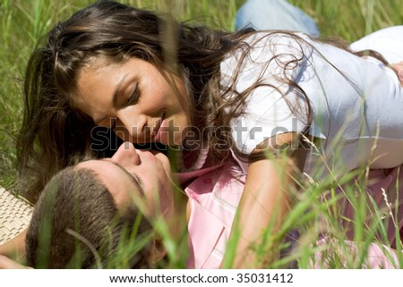 Photo of tender girl embracing her boyfriend while lying on grass - stock photo