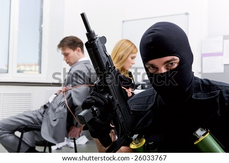 Photo of terrorist in balaclava holding gun on background of bound office workers - stock photo