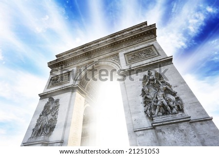 Photo of the Arc de Triomphe historical building in Paris flaring up with beautiful bright lights on a colorful cloudy sky background. Conceptual. - stock photo