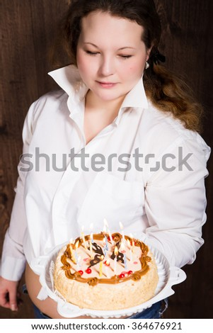 photo of The beautiful smiling young woman with a cake
