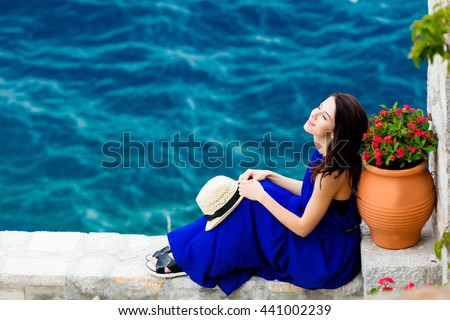 photo of the beautiful young woman sitting near the sea after sightseeing in Greece - stock photo