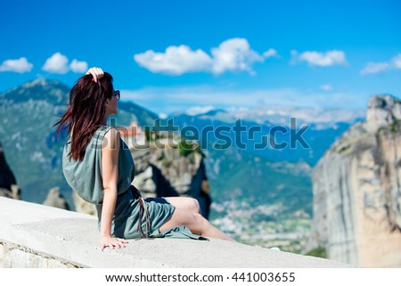 photo of the beautiful young woman sitting on the stone railing and looking at the splendid view in Greece