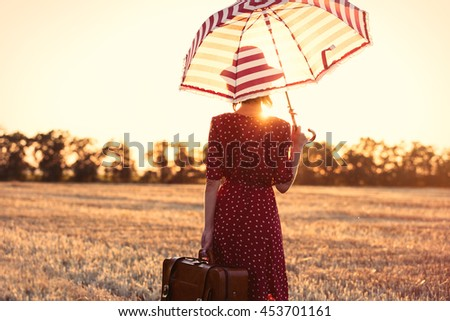 photo of the beautiful young woman with red umbrella and brown suitcase standing in the field - stock photo
