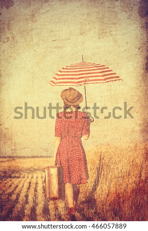 photo of the beautiful young woman with red umbrella and brown suitcase walking in the field