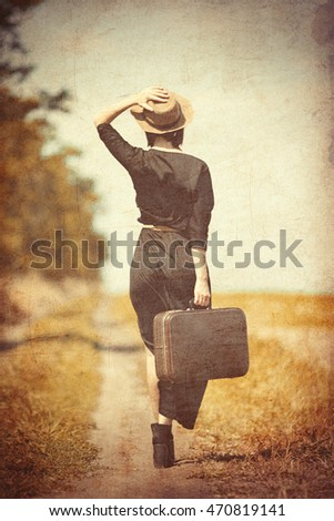 photo of the beautiful young woman with suitcase on the countryside road