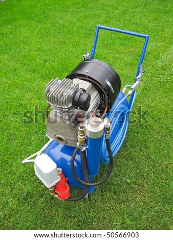 Photo of the blue mobile compressor on the green background - stock photo