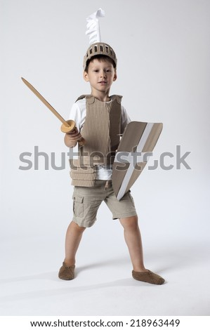 photo of the boy in medieval knight costume made of cardboards - stock photo