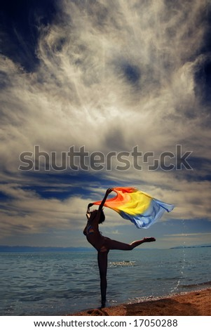 Photo of the dancing lady at the sea during vibrant sunset - stock photo