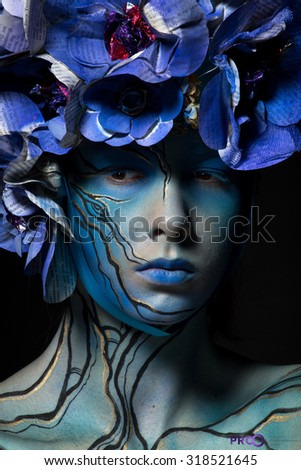 photo of the girl in blue body art image with colors from Newspapers on the head on a dark background