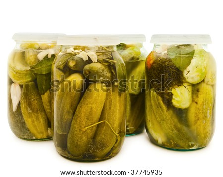 Photo of the glass jars with marinated cucumbers against the white background - stock photo