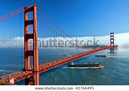 photo of the golden gate bridge in san francisco, usa. ship passing under golden gate bridge san francisco California . large shipping container ship in bay area.