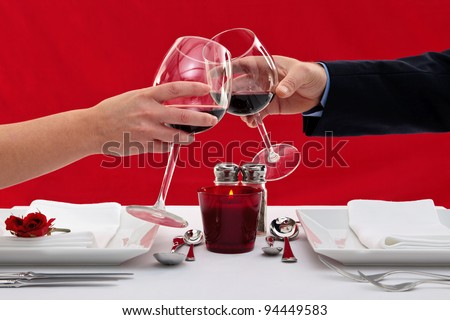 Photo of the hands of a married couple toasting their wine glasses over a restaurant table during a romantic dinner. - stock photo