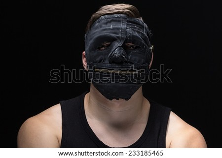 Photo of the man in handmade mask on black background