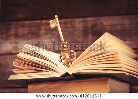 photo of the old books and key on the brown wooden background - stock photo