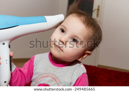 Photo of the Pretty curly toddler drying her hair
