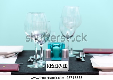 Photo of the reserved sign on a restaurant table setting. Focus is on the sign with a very shallow depth of field. - stock photo
