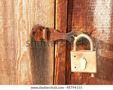 Photo of the rusty lock on a wooden door.