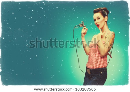 Photo of the sexy pin up girl, with tattoos, holding a tattoo machine. Copy space to the left of the subject. Retro styled imagery, toned image, added noise, vintage. - stock photo