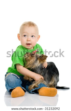Photo of the sitting little boy with a dog