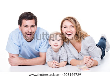 Photo of the smiling young parents with little child lying on the floor - isolated on white background. - stock photo