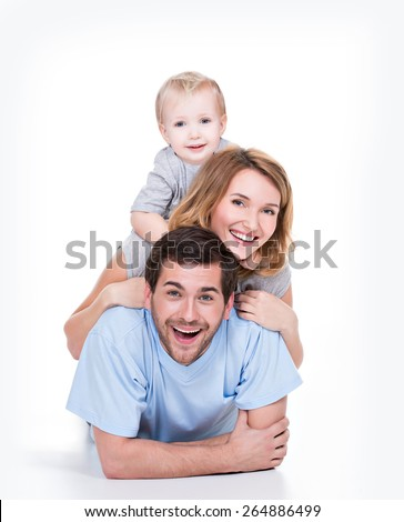 Photo of the smiling young parents with little child lying on the floor - isolated on white background.