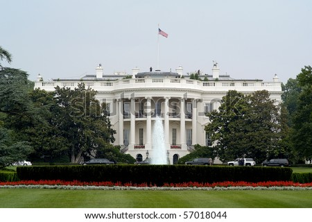 Photo of The White House in Washington DC taken from the street with a clear blue sky.  Includes landscape and fountain. - stock photo