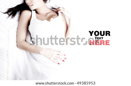 Photo of the  woman pampering on a white bed with a place for text - stock photo
