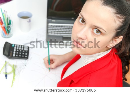 Photo of the Young female designer working with architectural plan in her modern home office
