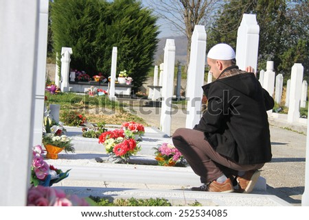 Photo of the Young muslim man near the his father grave