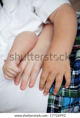 Photo of three arms side by side. They are the arms of children of varying ages. Vertically framed photo. - stock photo