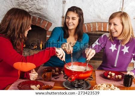Photo of three beautiful females dipping bread into the melted cheese in a fondue pot. - stock photo